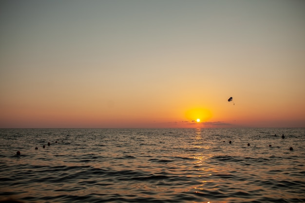 Silhouette of powered paraglider soaring flight over the sea against marvellous orange sunset sky.