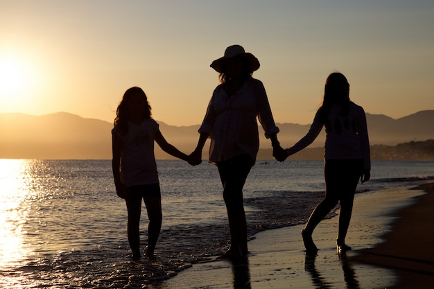 Silhouette of pregnant mother and daughters on the beach at sunset