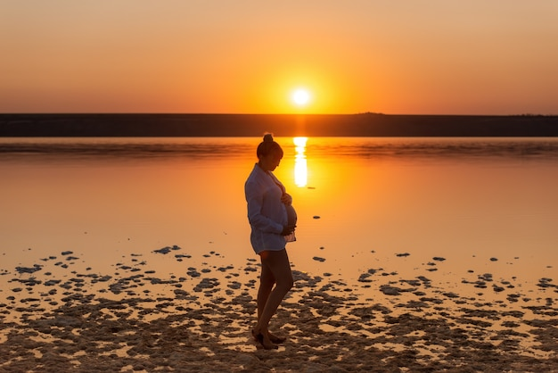 Silhouette of a pregnant woman on the beach at sunset. a pregnant girl against the background of the water
