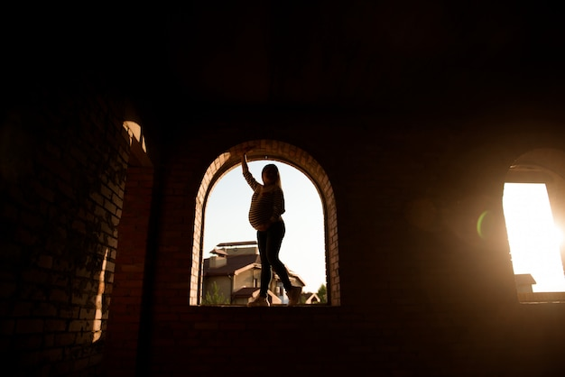 Silhouette of a pregnant woman at a sunset