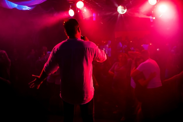 Silhouette of presenter with microphone in hand on stage at concert in nightclub