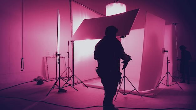 Silhouette production crew team working in photo shooting studio and lighting flash and led headligh