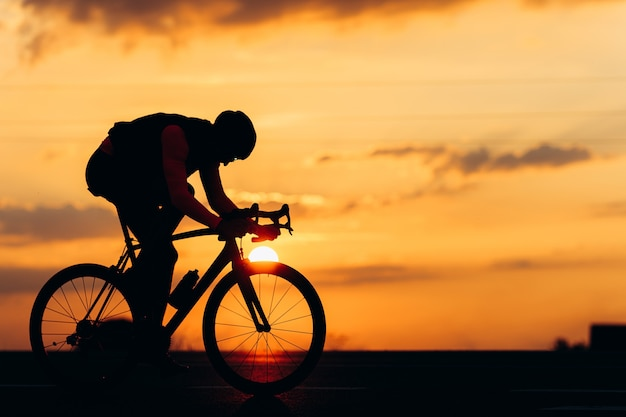 Silhouette of professional cyclist in protective helmet using bike for sport activity on paved road