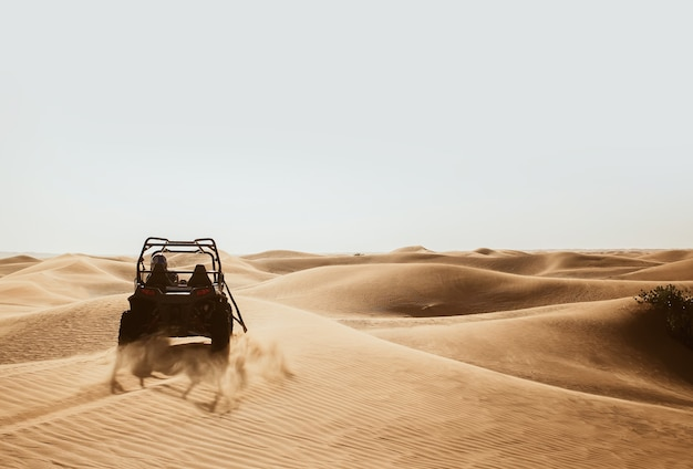 Silhouette of quad buggy bike drifting at safari sand dunes of al awir desert, dubai, uae