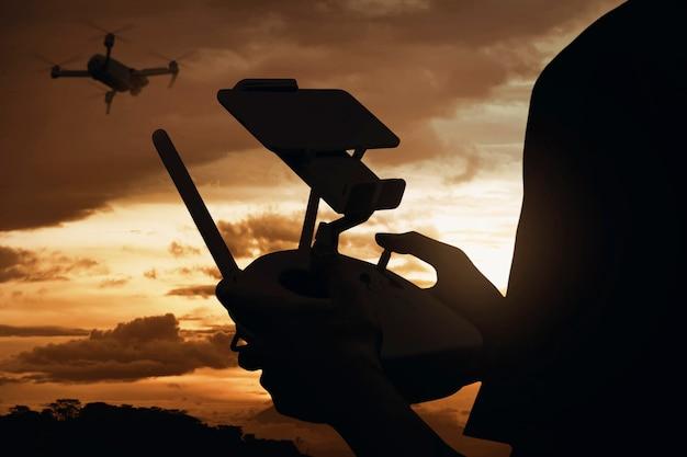 空を飛んでいるドローンを制御する男のシルエット背面図