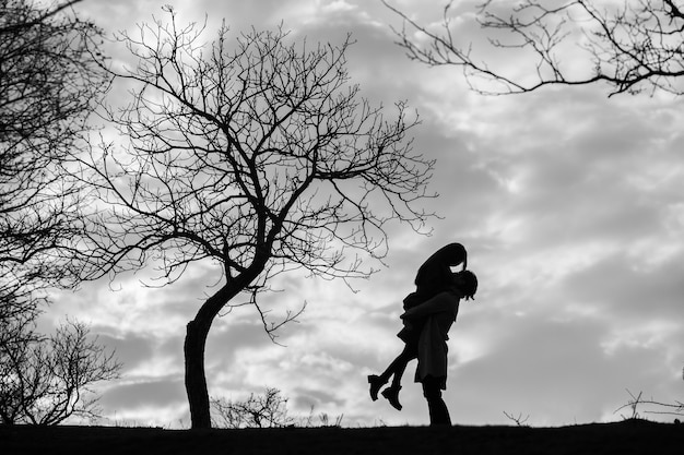 Silhouette of romantic couple in love man and women in sunset sky