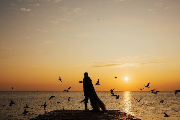 Silhouette of romantic couple of lovers hug and kiss at colourful sunset on surface.