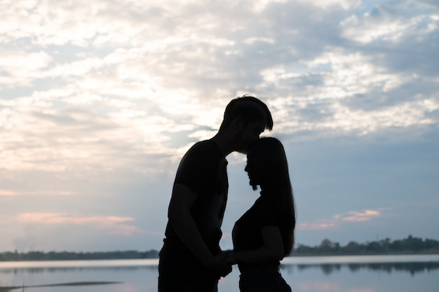 The silhouette of a romantic couple standing, hugging each other and watching the sunset.