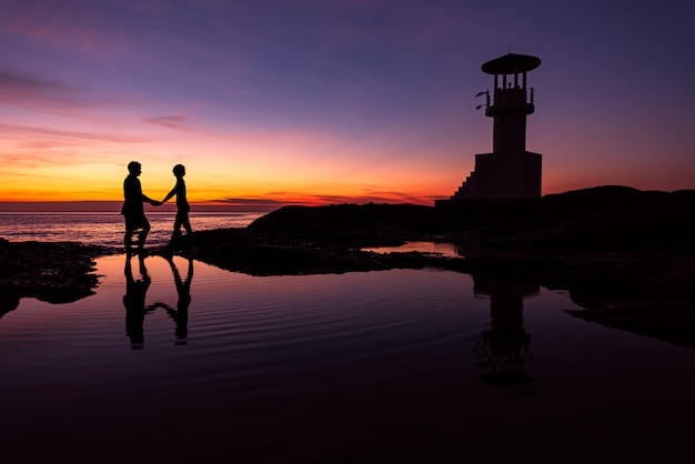 Silhouette romantic couple with lighthouse at sunset time