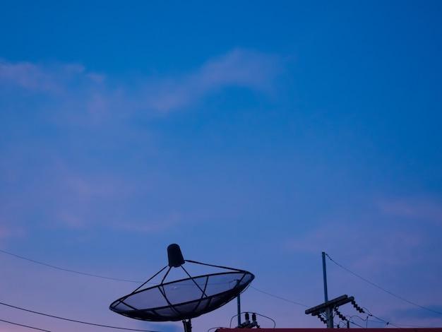 Силуэт спутниковой антенны на крыше здания с сумеречным голубым небом