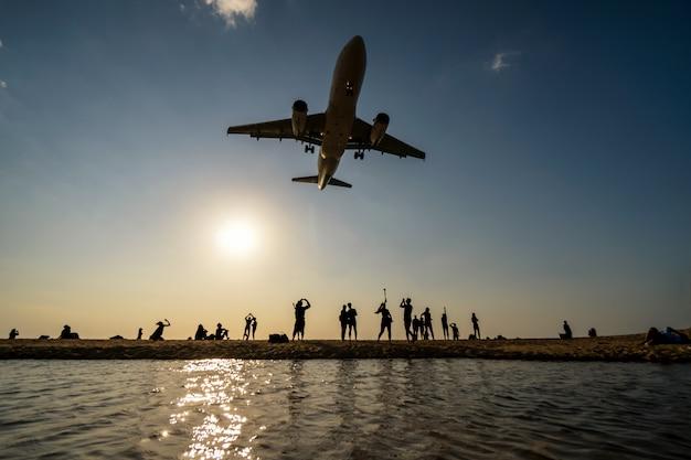 飛行機の地形を見て写真を撮っている旅行者のシルエット