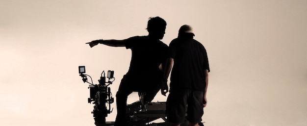 Silhouette behind the scenes of camera man and production team talking about shooting angle