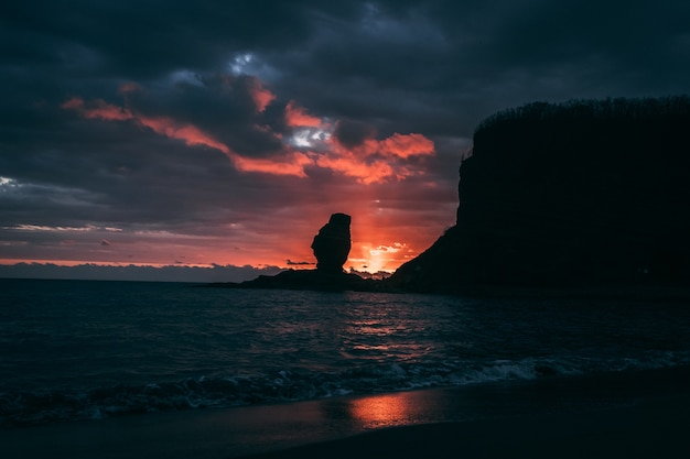 Silhouette of a sea stack against a colorful setting sun at new caledonia