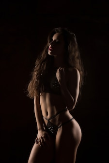 Silhouette of sexy fitness woman in black lingerie at studio