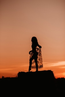 Silhouette of a sexy nude girl in underwear in a field in summer at sunset in nature on a haystack. added the effect of a small film grain