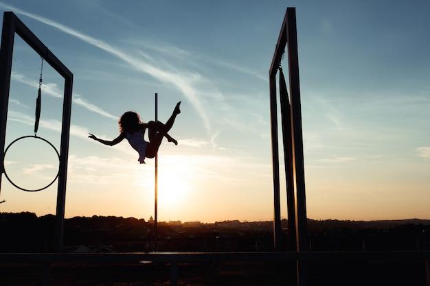 Siluetta del ballerino del palo sexy che esegue sul tetto al tramonto