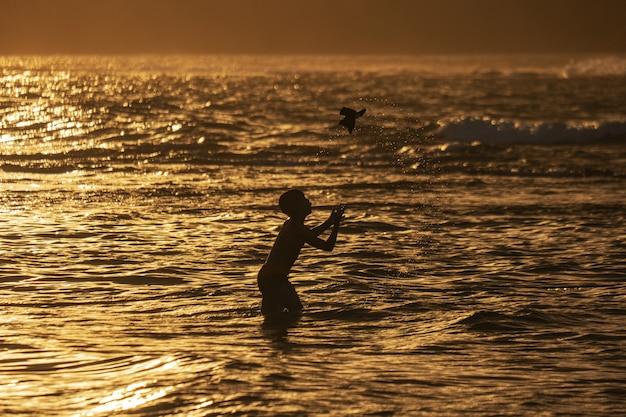Силуэт выстрел мальчика, играющего на пляже