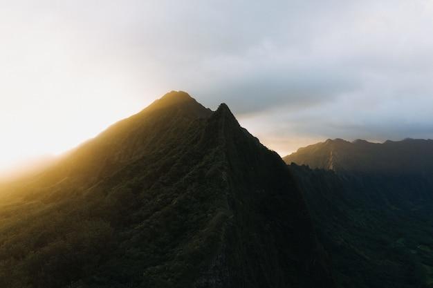 Силуэтный снимок крутой горы с закатом в пасмурном голубом небе