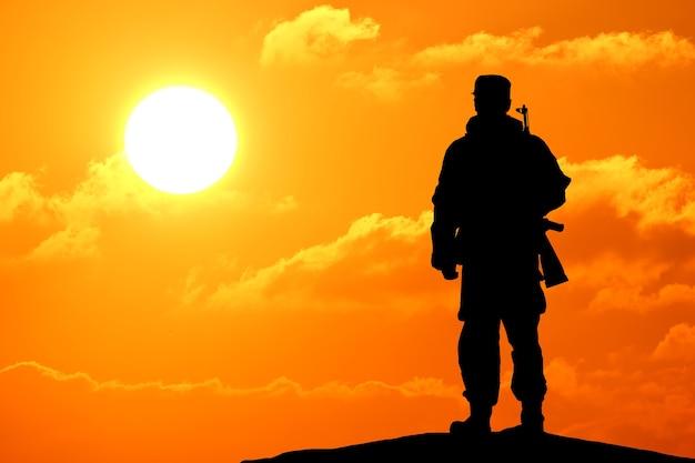 화려한 하늘과 산을 배경으로 총을 들고 있는 군인의 실루엣 샷