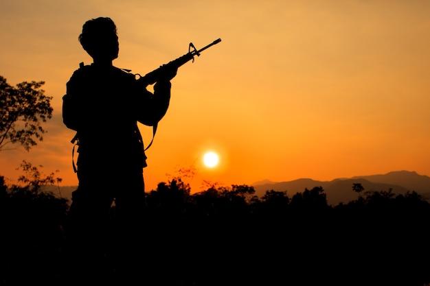 Силуэт выстрел солдата, держащего пистолет