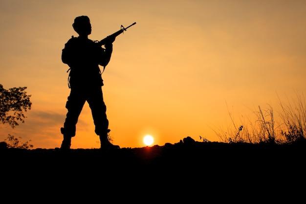 Силуэт выстрел солдата, держащего пистолет Premium Фотографии