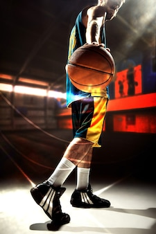 The silhouette side view of a basketball player holding basket ball on dark background