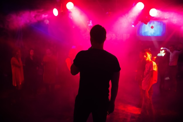 Silhouette of the singer against a crowd of people at a party in a nightclub