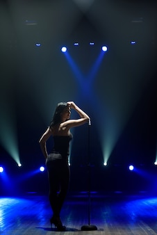 Silhouette of singer standing on stage at microphone in night club.