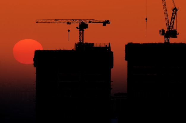 Silhouette of skyscraper under construction with crane at twilight sunset background