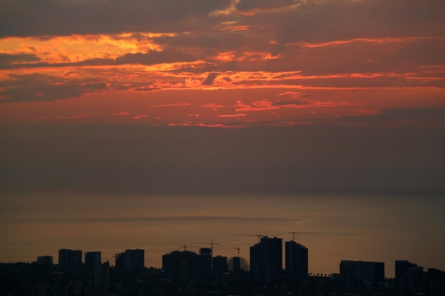 Silhouette of skyscrapers and construction area with sunset sky over the sea