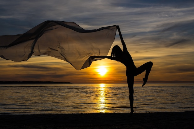 Silhouette of slim sexy girl posing with scarf on the beach at sunset