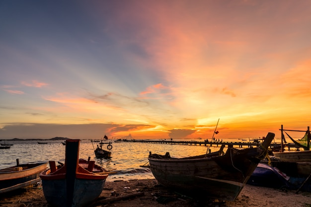 Silhouette small fishing boat at shore in sunset at bang phra beach,sriracha choburi,thailand