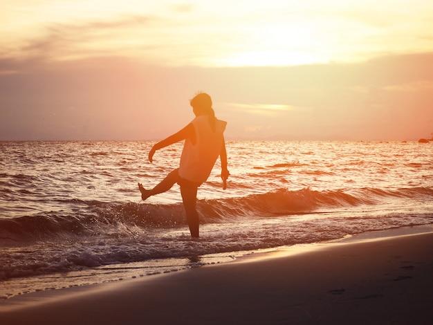 シルエット笑顔の女性がビーチで水の波を蹴ります。