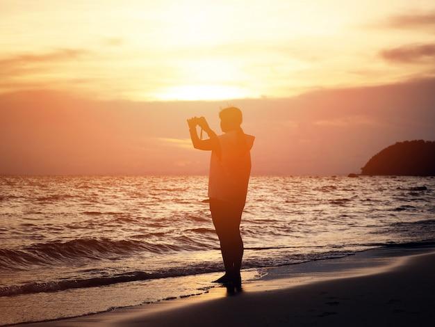 シルエット笑顔の女性がビーチで写真を撮る。