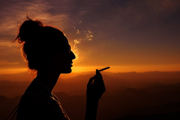 Silhouette of smoking woman in sunset landscape