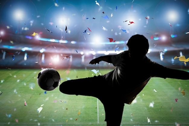 Силуэт футболиста ногами по мячу на фоне стадиона