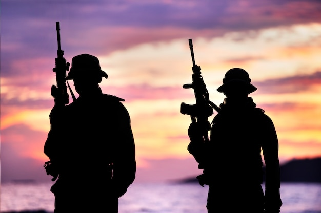 Silhouette of soldier carrying gun