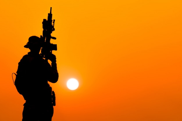 Silhouette of soldier in sunset sky. soldier with machine gun patrolling