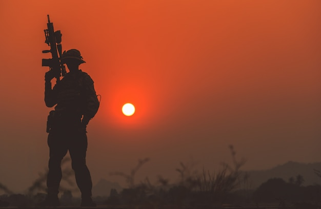 Silhouette of soldier in sunset sky.soldier with machine gun patrolling