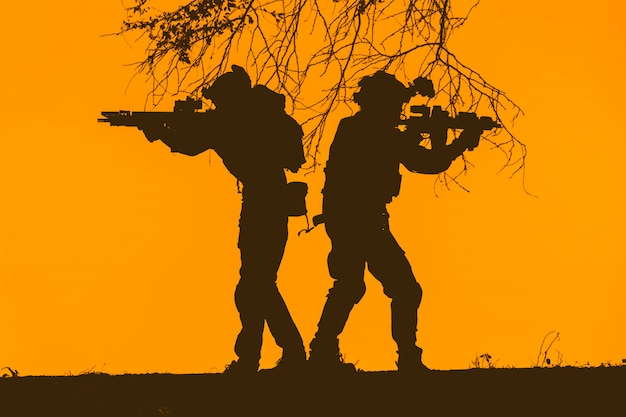 Silhouette of soldier team, sunset sky. soldier with machine gun patrolling