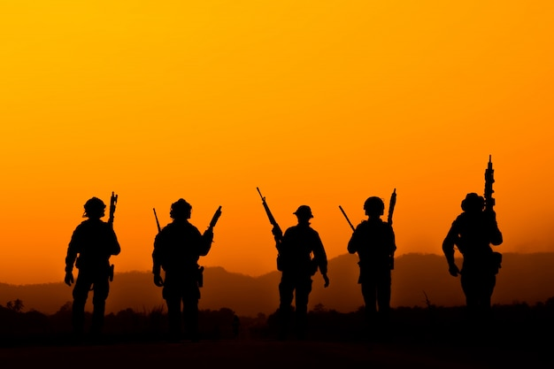 Silhouette of soldier team in sunset sky. soldier with machine gun patrolling