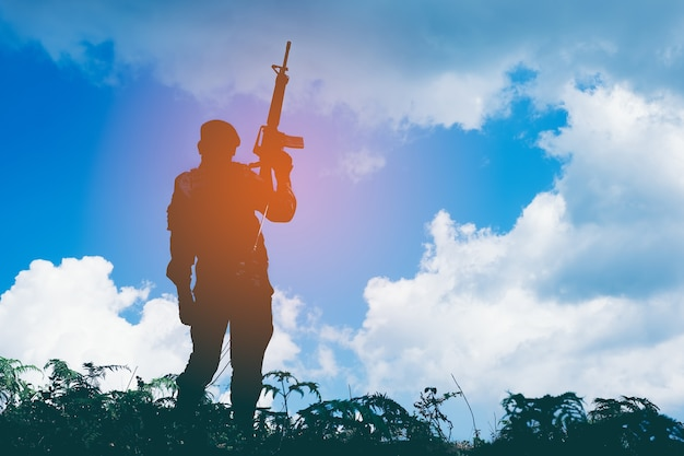 Silhouette of soldier with rifle against the sun