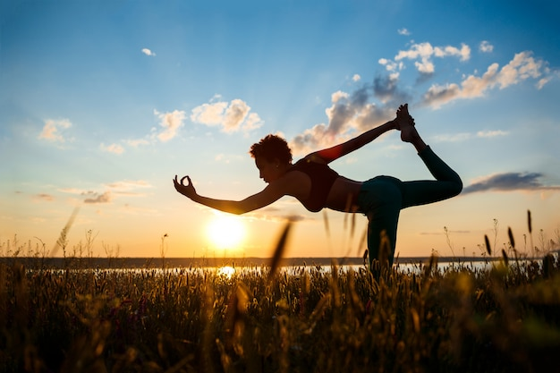 Silhouette of sportive girl practicing yoga in field at sunrise.