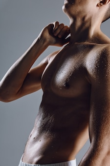Silhouette of sportive man on gray background naked torso bodybuilder