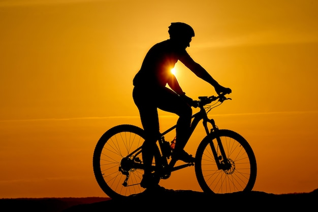 Silhouette of a sporty cyclist in helmet on a bike