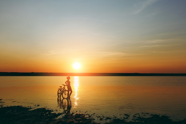 The silhouette of a sporty girl in a suit standing near a bicycle in the water at sunset on a warm summer day. fitness concept.