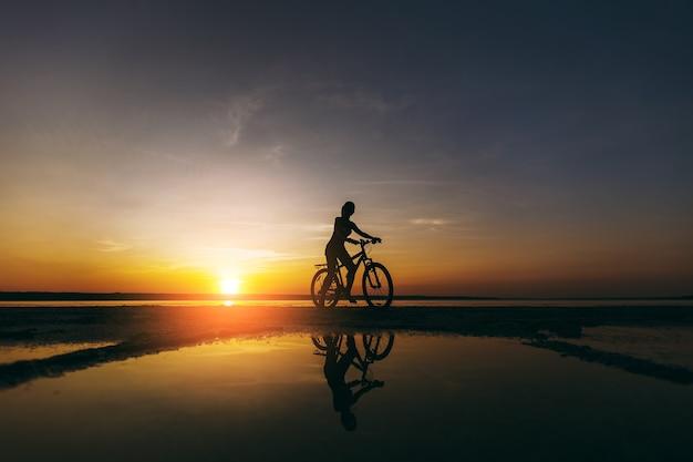 La silhouette di una ragazza sportiva in un vestito che si siede su una bicicletta nell'acqua al tramonto in una calda giornata estiva. concetto di forma fisica.