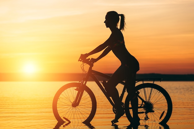 The silhouette of a sporty girl in a suit that sits on a bicycle in the water at sunset on a warm summer day. fitness concept.