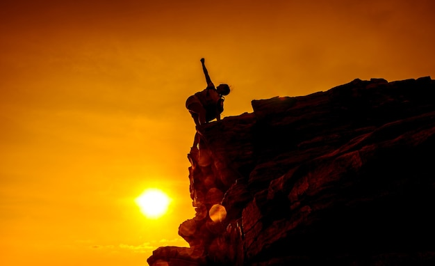 Silhouette sporty woman on the cliff. sunset and high mountain. business success and goal.
