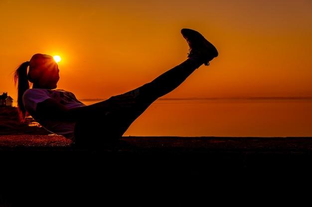 Силуэт спортивный женщина с закатом. здоровая и физическая активность. образ жизни и отдых.